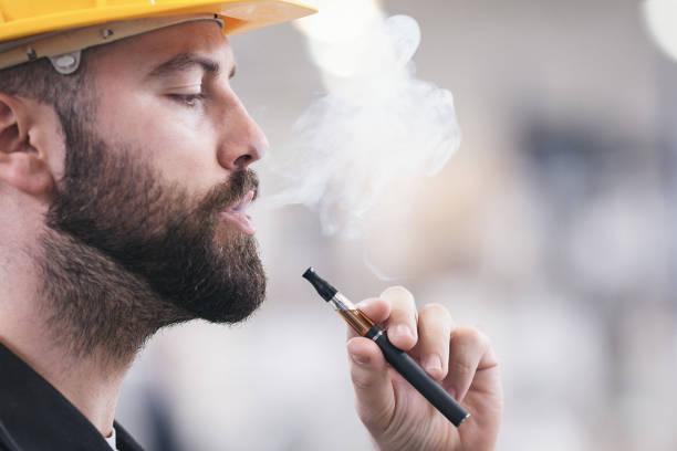 Junge männliche Arbeiter rauchen elektronische Zigarette – Foto