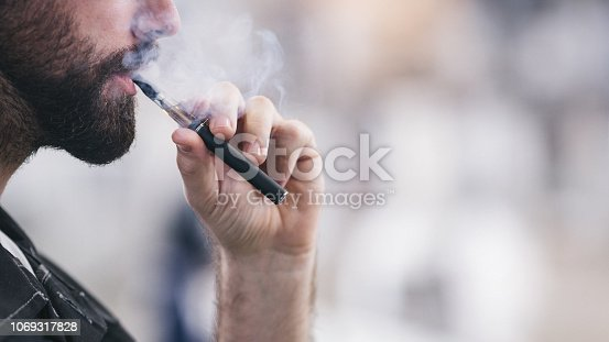 Smoking electronic cigarette. Shallow DOF. Developed from RAW; retouched with special care and attention; Small amount of grain added for best final impression. 16 bit Adobe RGB color profile.
