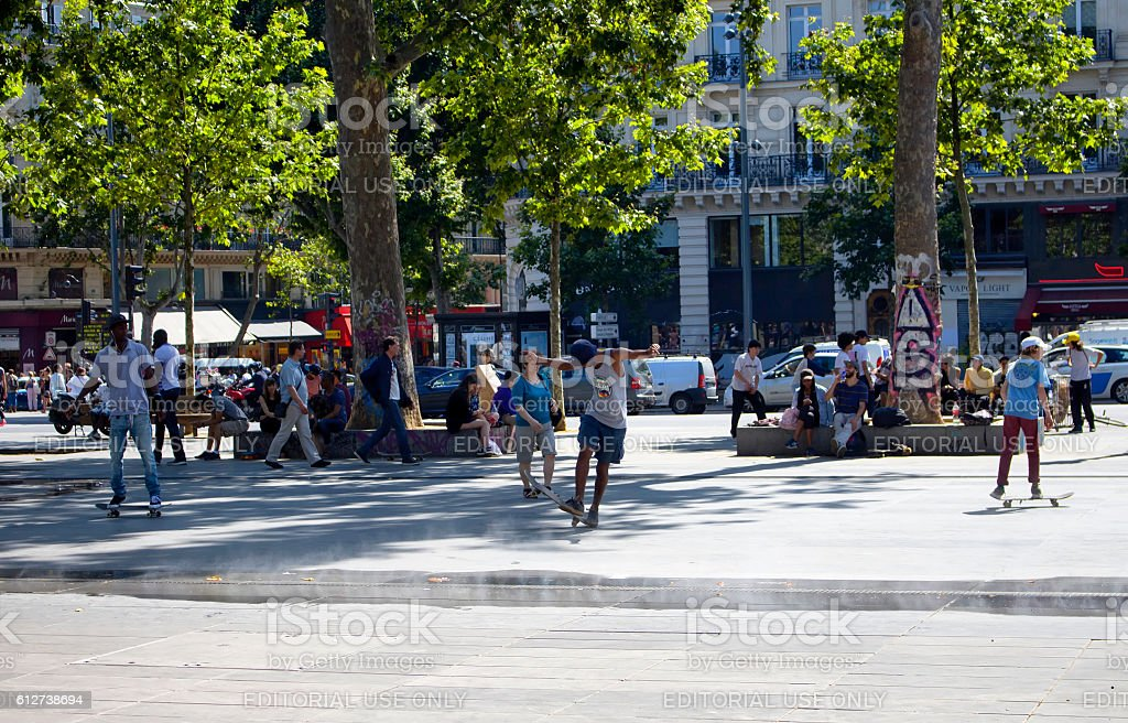 Young males skate at Republic Square in Paris. stock photo