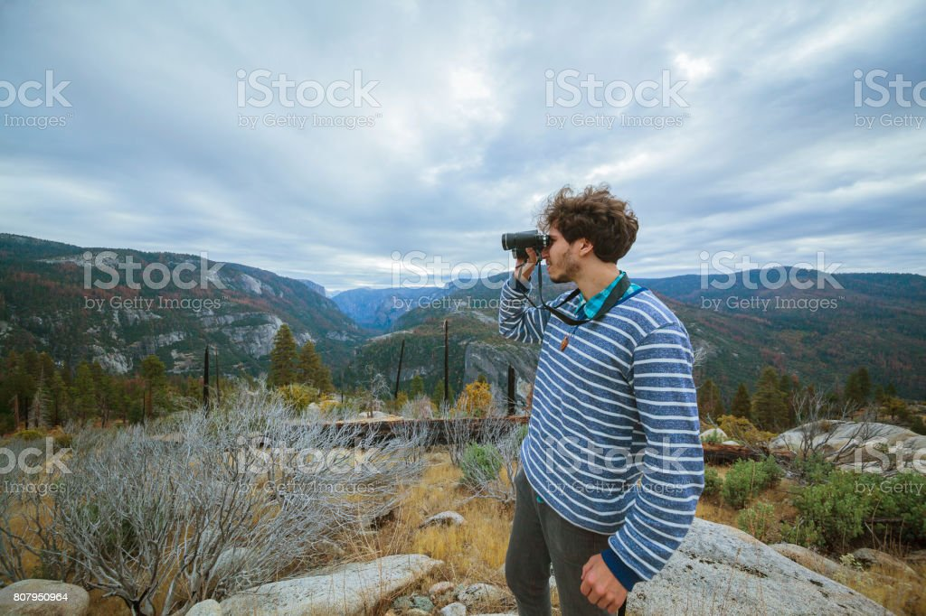 Young man, 25-years-old traveling hipster, observing the nature with the binocular from the elevated rocky point near by Devil Dance Floor in the Yosemite National Park stock photo