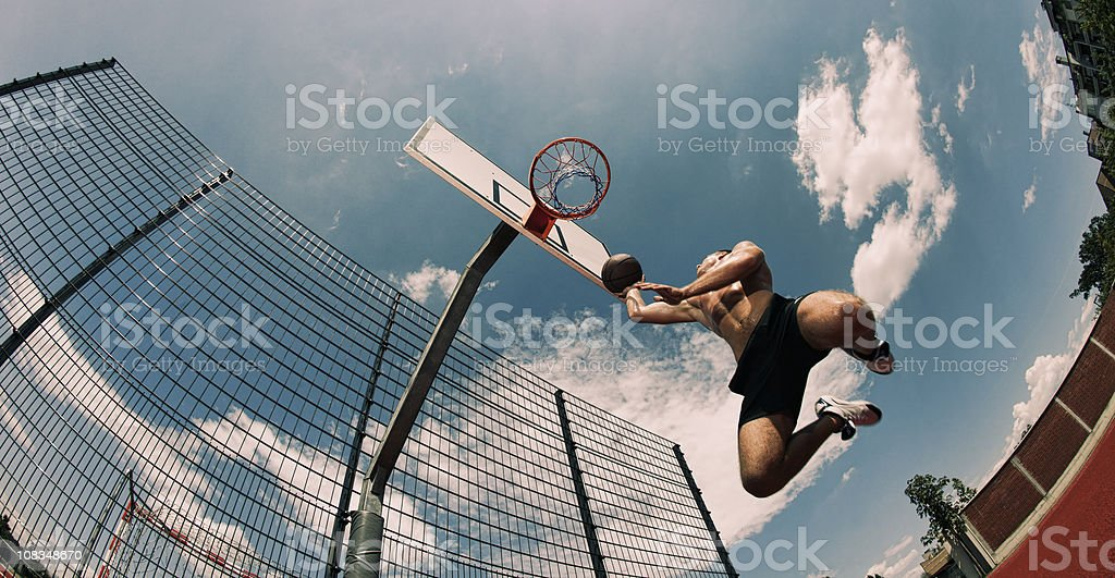 Young man about to slam dunk stock photo