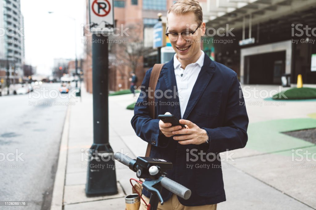 young man about to use a shared electric scooter stock photo