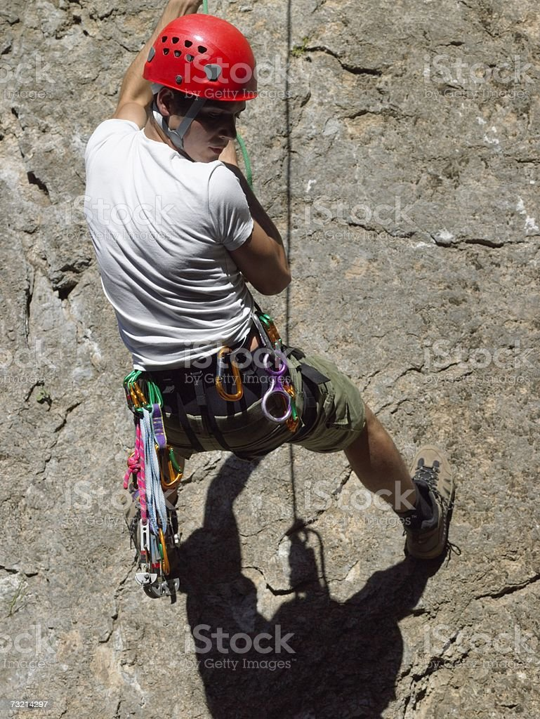 Young man abseiling down cliff royalty-free stock photo