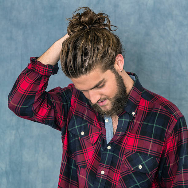 Young Man Adjusting Hair Bun Studio portrait of a handsome young metrosexual man with long, tousled brown hair and a full beard wearing a plaid lumberjack shirt open at the collar. He's looking down with his arm raised and his hand adjusting the