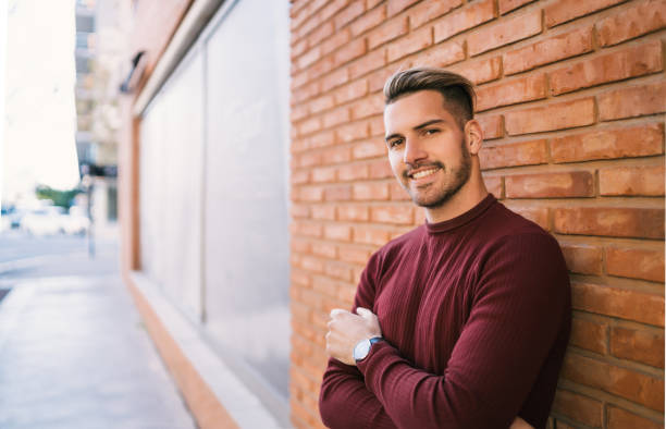 Young man against brick wall. stock photo