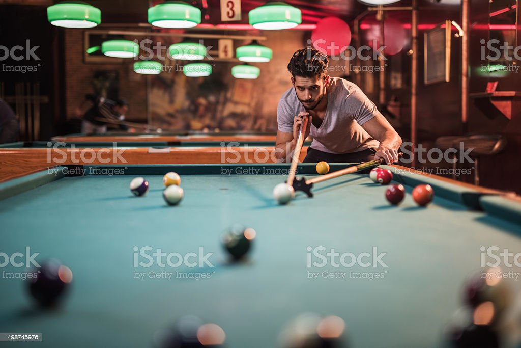 Man playing billiard in a pool hall with a support of another cue.