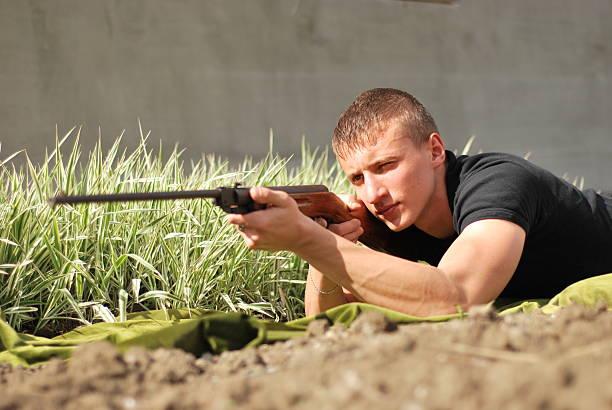 young man aiming with a hunter gun stock photo