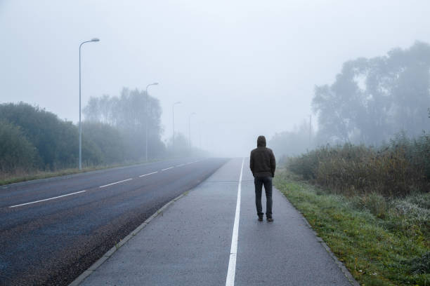 young man alone walking on sidewalk in mist of early morning. foggy air. go away. back view. - one man only stock pictures, royalty-free photos & images