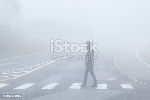Young man alone without reflector elements crossing street on crosswalk in mist of early morning. Poor visibility. Foggy air. Side view.