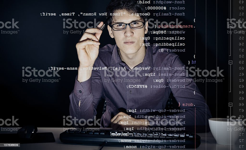 young man analyzing his css definitions young man with glasses sitting in front of his computer, programming. the code he is working on (CSS) can be seen through the screen. 20-29 Years Stock Photo