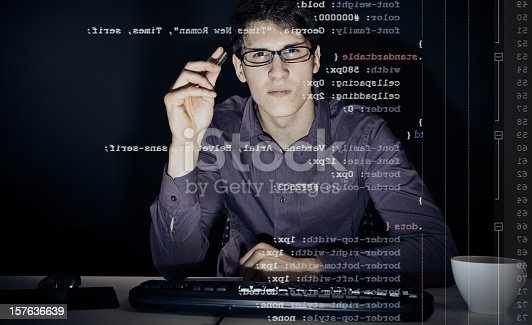 young man with glasses sitting in front of his computer, programming. the code he is working on (CSS) can be seen through the screen.