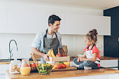 Father and daughter with healthy food on the kitchen counter.