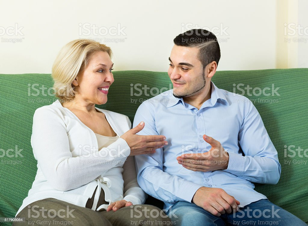 Young man and aged woman talking indoor stock photo