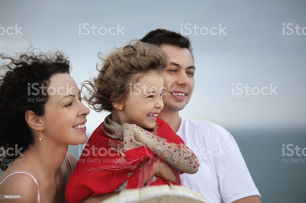 Young man and beautiful woman protects little girl from wind royalty-free stock photo