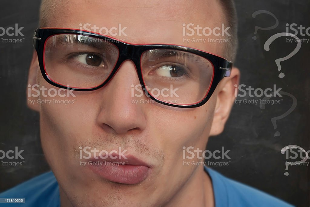 Young man and blackboard filled with question marks royalty-free stock photo