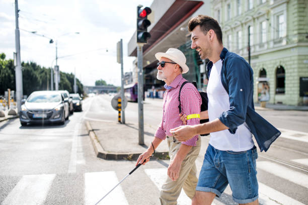 young man and blind senior with white cane walking in city, crossing street. - pedone ruolo dell'uomo foto e immagini stock