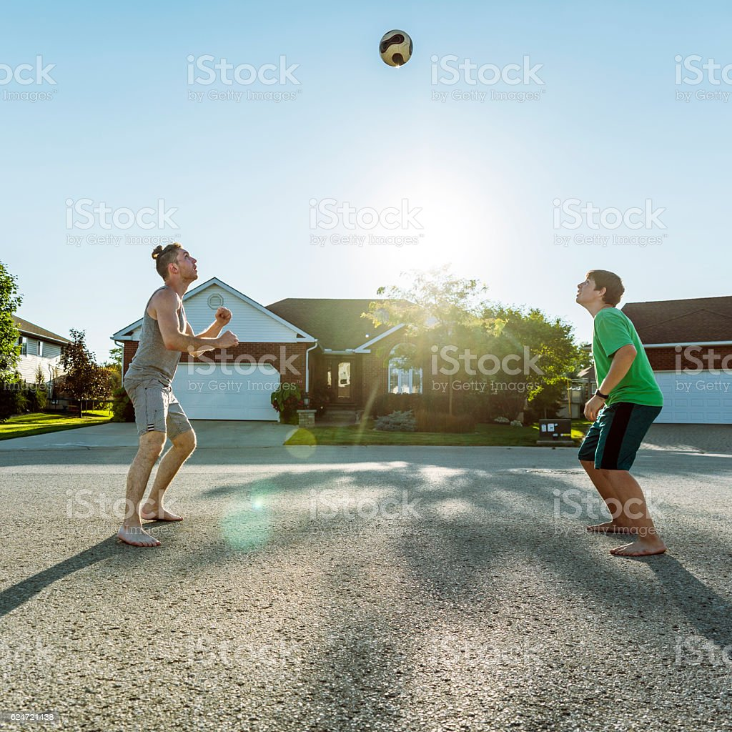 Young man and boy playing volleyball in neighborhood, Ontario, Canada stock photo