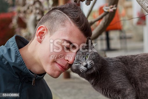 istock Young man and cat making friends - color version 534406884