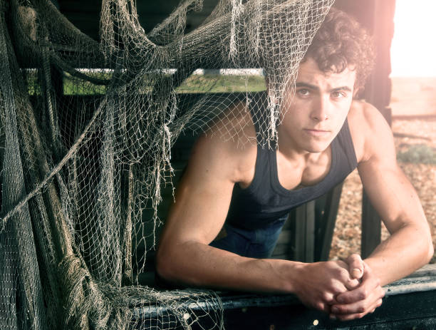 young man and fishing nets stock photo