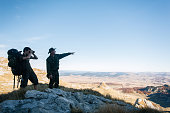 istock Young man and guide use binoculars in mountains 1191375445