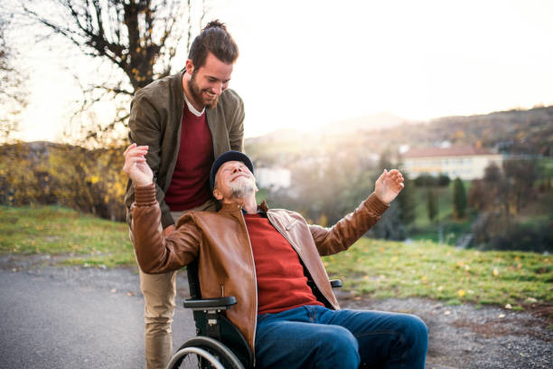 young man and his senior father in wheelchair on a walk in town. - personale sanitario foto e immagini stock