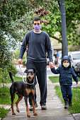 Young man and his son walking their  doberman pet wearing a protective mask