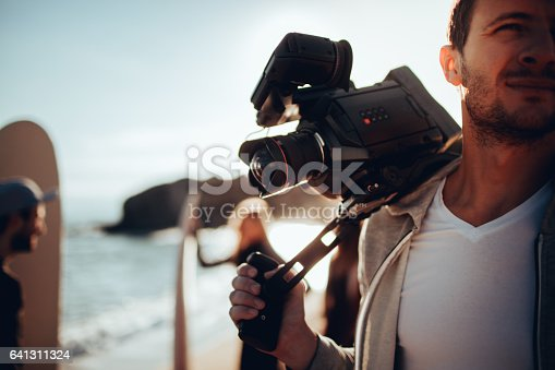 Young man holding video camera, having a photo shoot with his friends at the beach, while they are preparing to surf