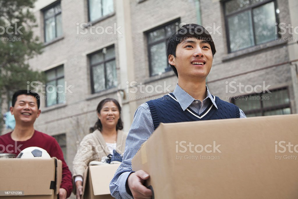 Young man and parents moving boxes into a college dormitory stock photo
