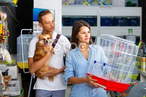 young man and smiling woman with dog is looking a cage for canary bird from assortment in pet shop