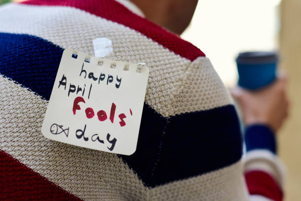 young man and text happy april fools day closeup of a young caucasian man seen from behind having a coffee, with a note with the text happy april fools day attached with tape to his back april fools day stock pictures, royalty-free photos & images