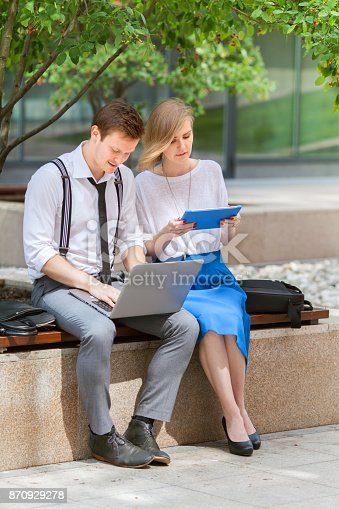 557608497istockphoto A young man and woman are working on bench in office center's yard 870929278