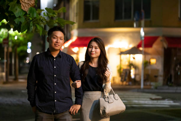 Young man and woman crossing arms against night cityscape background stock photo