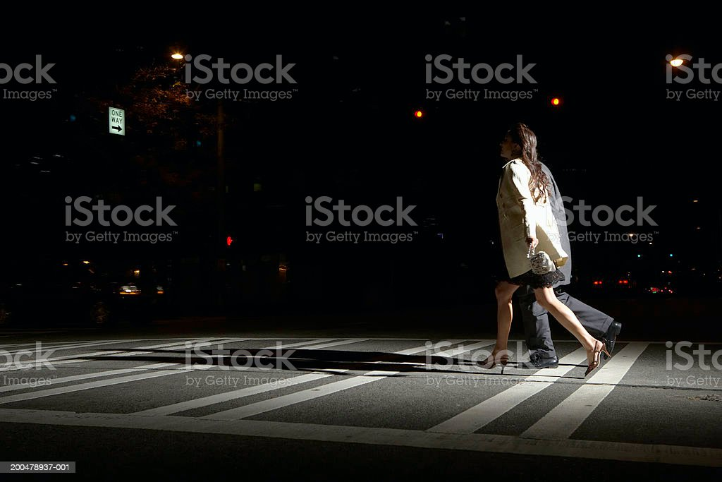 Young man and woman crossing street at night, side view stock photo