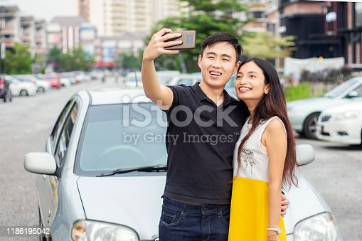 972962180 istock photo Young Man And Woman Do Selfie Near Their New Car 1186195042