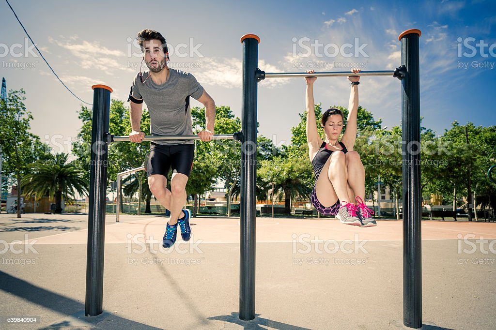 Young man and woman doing exercise in a city park stock photo