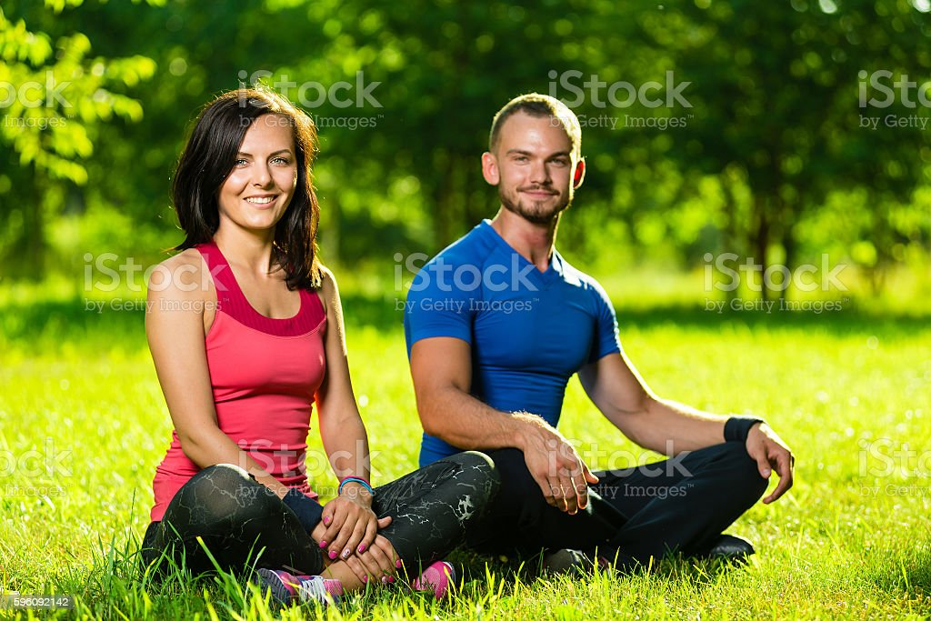 Young man and woman doing yoga in the sunny summer royalty-free stock photo