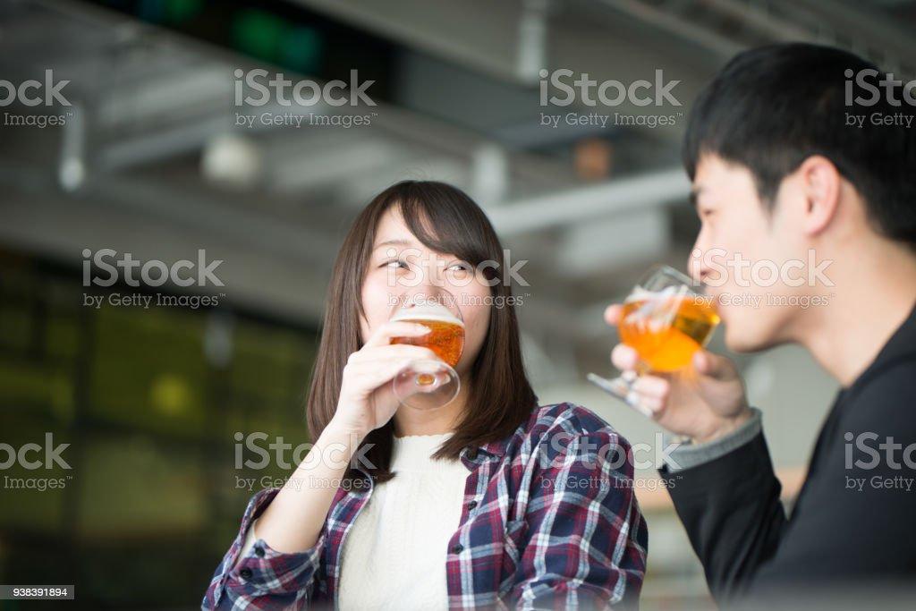 若い男とハッピーアワーでビールを飲む女性 ストックフォト