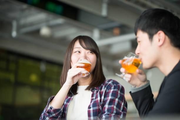 jonge man en vrouw drinken bier op happy hour - heteroseksueel koppel stockfoto's en -beelden