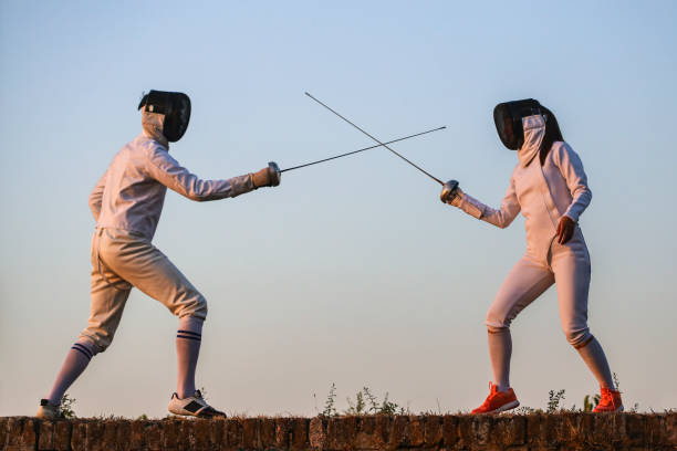 Young man and woman fencing stock photo