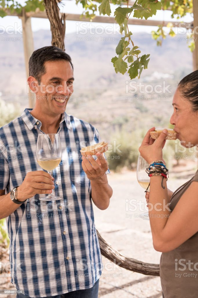 A young man and woman having bread and wine stock photo