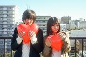若い男と女の都市屋上に赤いハートのバルーンを抱き締める