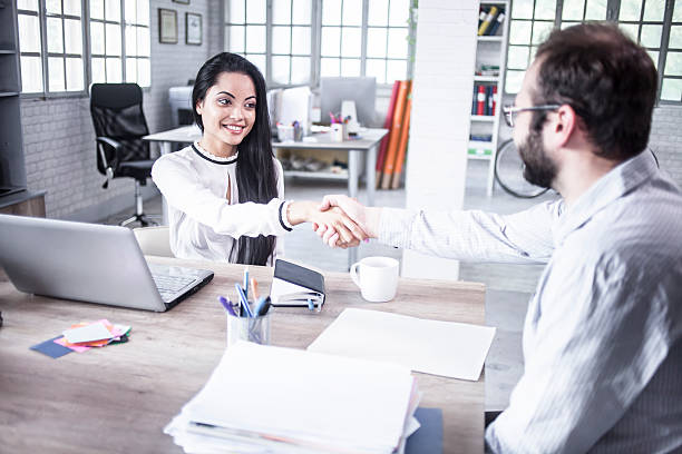 Young man and woman in handshake in the office - foto de acervo