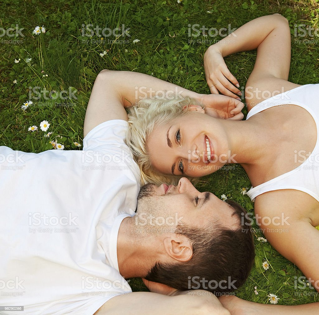 Young man and woman in love laying in a field royalty-free stock photo