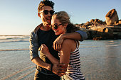 Outdoor shot of romantic young couple together on beach. Young man and woman in love on seashore.