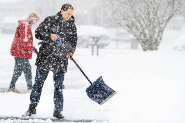 Young man and woman in winter coat cleaning shoveling driveway street from snow in heavy snowing snowstorm with shovel and abstract blurry blurred snowflakes falling stock photo