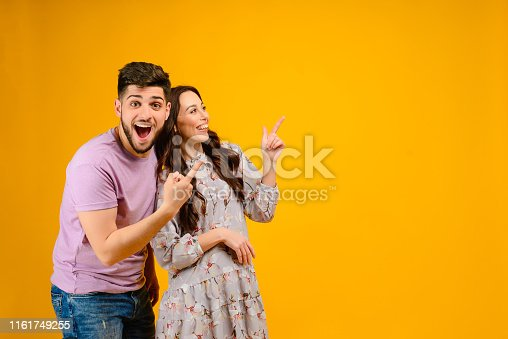 Photo of young couple man and woman smiling pointing at copyspace isolated over yellow background