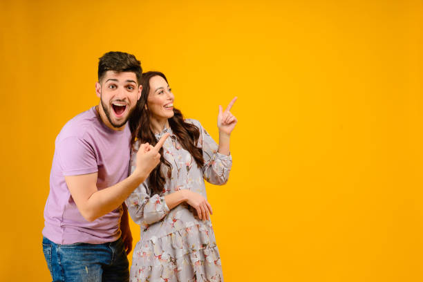 young man and woman isolated over bright yellow background - sorpresa foto e immagini stock