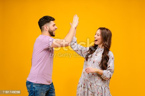 Photo of young couple man and woman giving high five isolated over yellow background