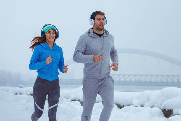 Young man and woman jogging on a snowy day in city stock photo