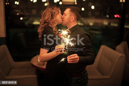 istock Young man and woman kissing and keeping bengal lights. 653164516